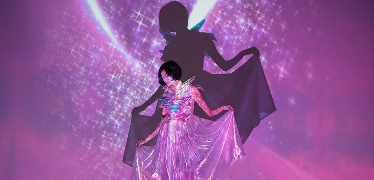 """Collaboration between Media Art Nexus and Singapore fashion designer Josiah Chua and his 2018 capsule collection, titled """"光"""" Hikari. For this SG:IO exhibition, Media Art Nexus, and Josiah created an interactive projection of dazzling stars and light that moves with the viewer, all to evoke that specific magic of Sailor Moon's transformation titled Crepuscular rays of the Moon"""